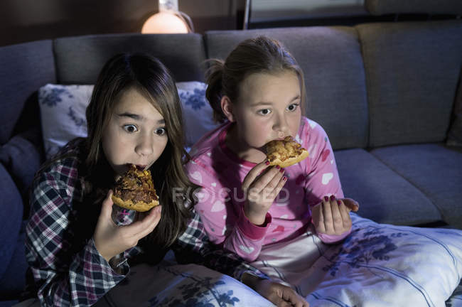 Girls eating pizza watching film — Stock Photo
