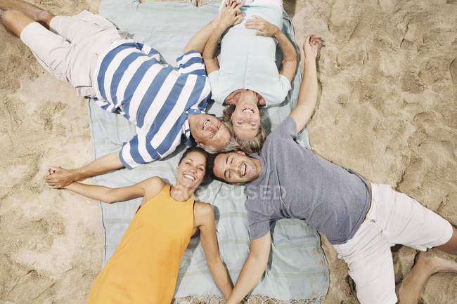 Sonriente familia acostada en la playa de arena - foto de stock