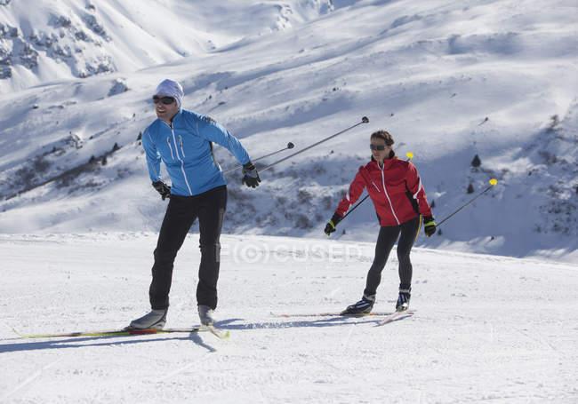Мужчина и женщина, Катание на лыжах в снежных горах — стоковое фото