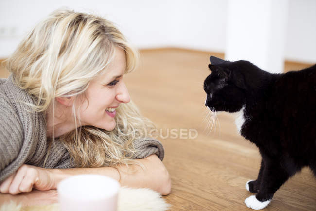 Young woman with cat on floor, smiling — Stock Photo
