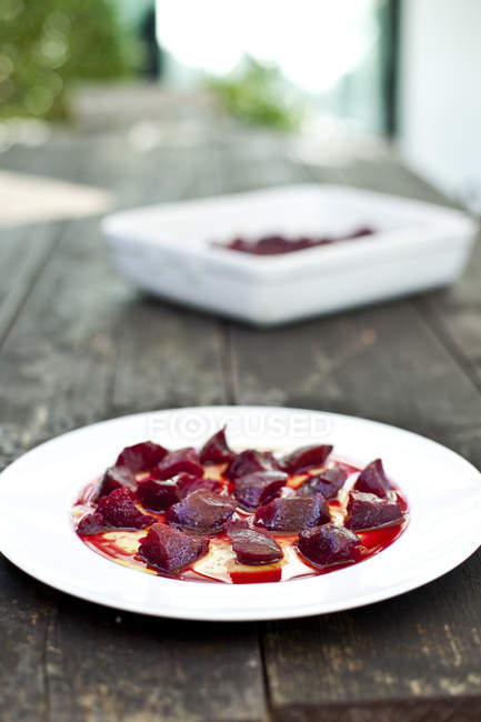 Plate of beetroot with vinaigrette over wooden surface — Stock Photo