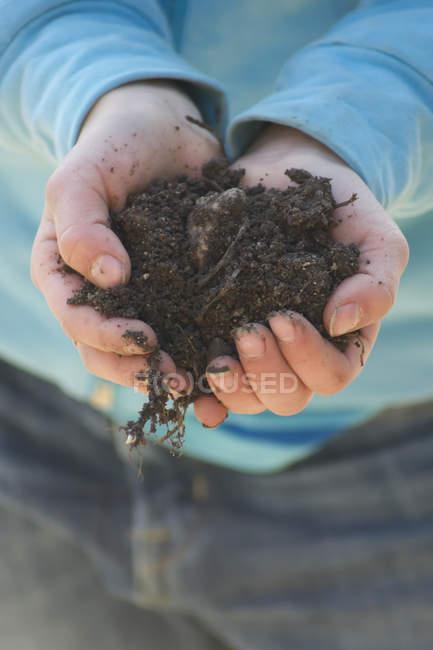 Ragazza mani in possesso di terreno — Foto stock