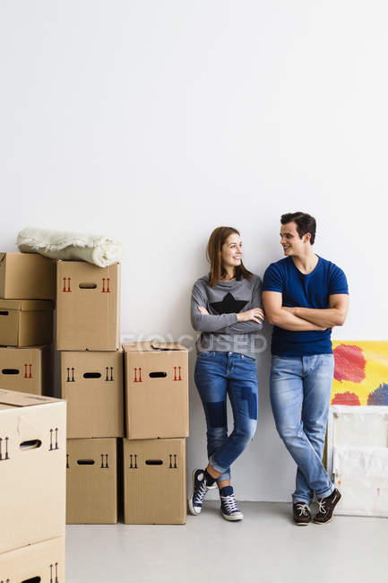 Smiling Young couple standing leaning on wall with cardboard boxes — Stock Photo