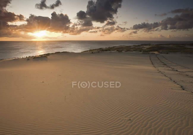 Lithuania, Sunrise on beach over water — Stock Photo