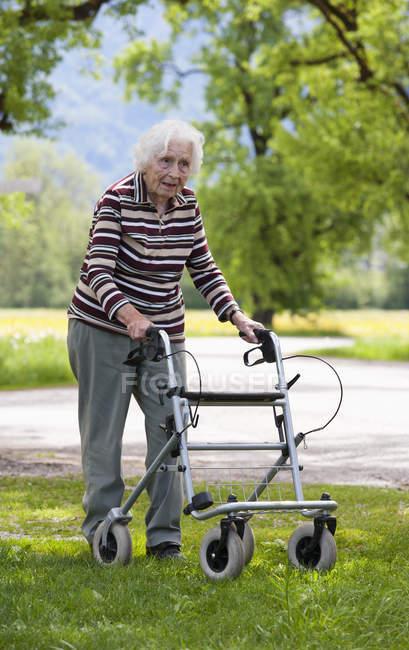 Senior woman pushing walking frame — Stock Photo