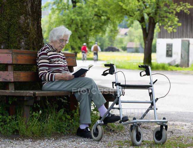 Femme âgée assise sur un banc et lisant un livre — Photo de stock