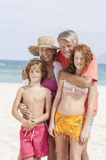 Grandparents with grandchildren standing on beach — Stock Photo