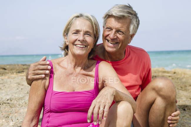 Coppia anziana seduta sulla roccia in spiaggia, sorridente — Foto stock