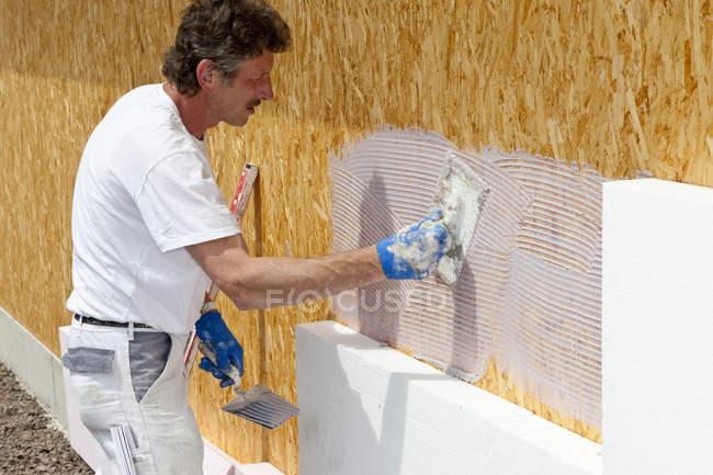 Man insulating polystyrene on construction site — Stock Photo