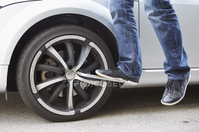 Germany, Bavaria, Kaufbeuren, Mature man changing car tire — Stock Photo