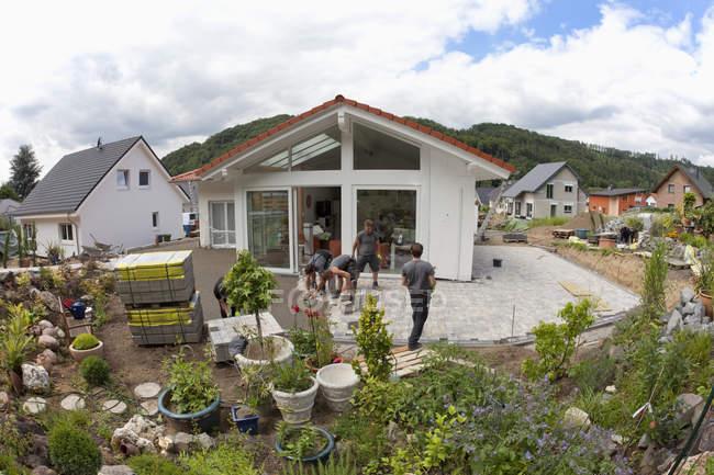 Jovens montando pedras de pavimentação na construção civil — Fotografia de Stock