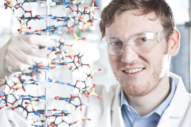 Closeup portrait of young scientist with DNA model, smiling at laboratory — Stock Photo