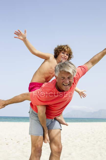 Grand-père donnant le tour de dos de porc au petit-fils — Photo de stock