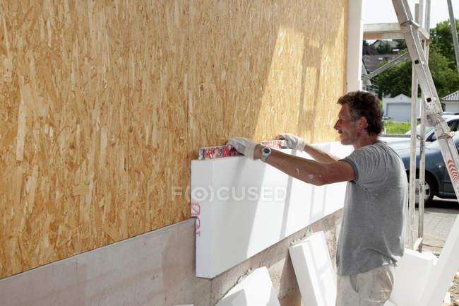 Людина прилипання полістиролу стіни дерев'яного будинку — стокове фото