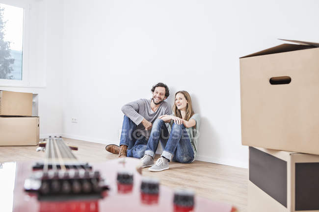 Coppia seduta sul pavimento con scatole mobili — Foto stock
