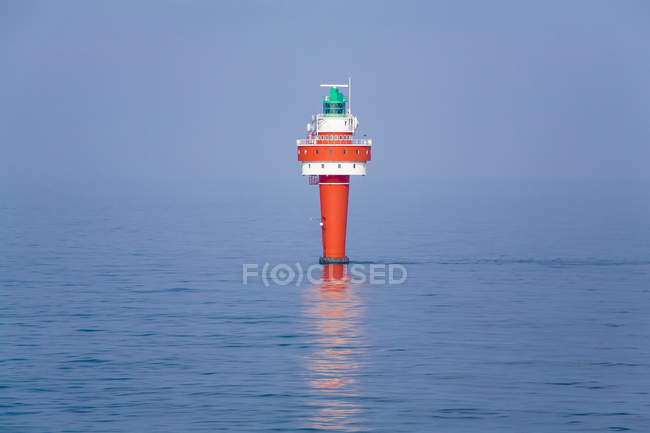 View of red light buoy with green signal light in sea — Stock Photo