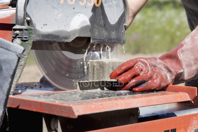 Young man cutting paving stone with saw — Stock Photo