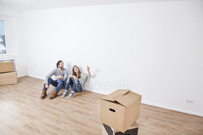 Couple sitting on floor with and pointing at wall — Stock Photo