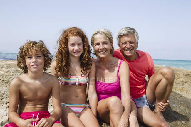 Бабушка и дедушка с внуками сидят на пляже — стоковое фото