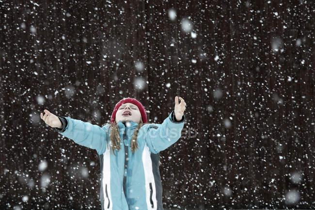 Девушка пытается ловить снежинки — стоковое фото