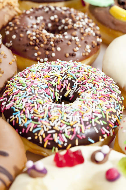 Close-up of sweet doughnuts with chocolate icing and sprinkles — Stock Photo