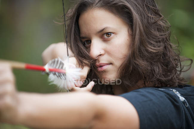 Young woman aiming arrow, close up — Stock Photo