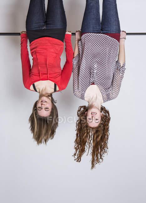 Young women hanging upside down, smiling — Stock Photo