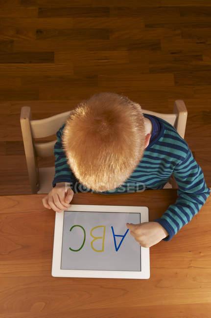 Вид сверху на мальчика с помощью цифрового планшета — стоковое фото
