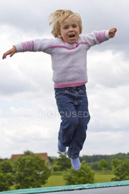 Little girl jumping on trampoline with arms outstretched — Stock Photo