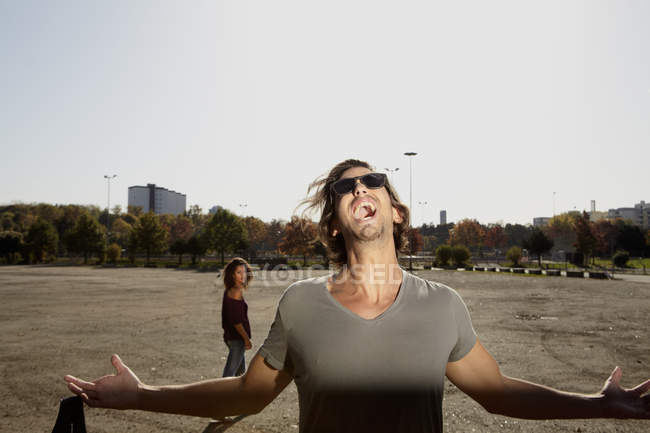 Man shouting and woman standing in background — Stock Photo