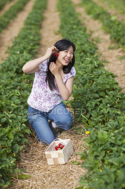 Женщина кладет клубнику в серьги — стоковое фото