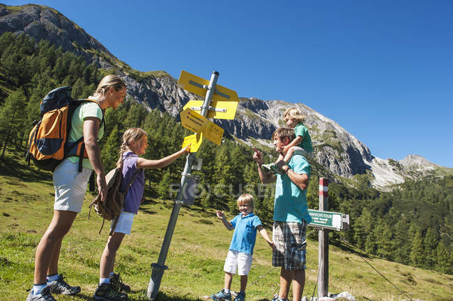 Family looking at signpost in mountains — Stock Photo