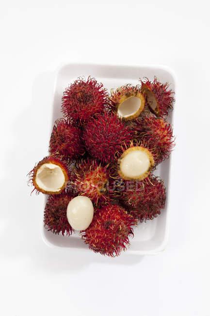 Frutas frescas de rambután de todo y a la mitades - foto de stock