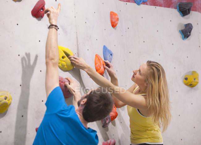 Jeune homme aidant femme à grimper sur le mur d'escalade — Photo de stock