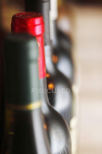 Close-up de garrafas de vinho borradas em linha — Fotografia de Stock