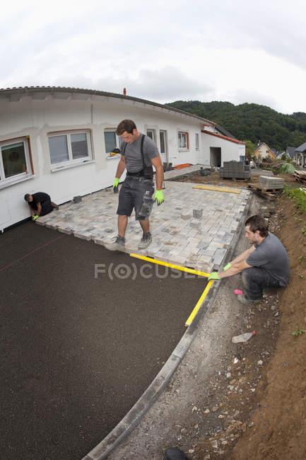 Giovani uomini che assemblano pietre da pavimentazione sulla costruzione di edifici — Foto stock