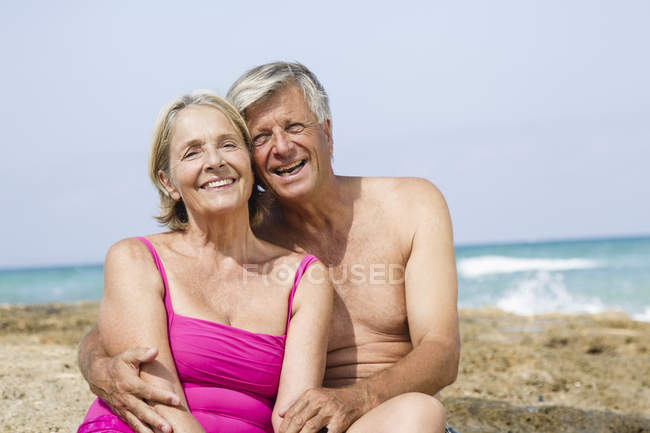 Senior couple sitting on rock at beach, smiling — Stock Photo