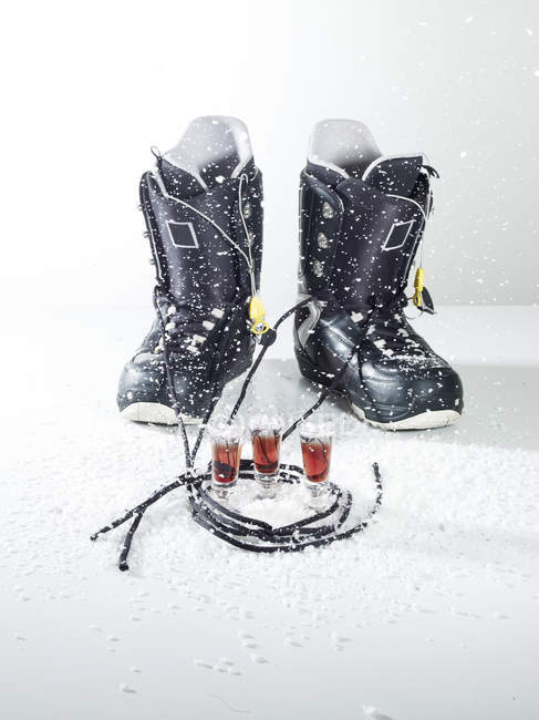 Snowboard shoes with drink on white background — Stock Photo