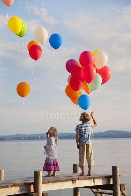Хлопчик і дівчинка, стоячи на пристані з літаючих повітряних куль на Штарнберг озеро — стокове фото