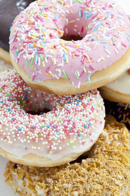 Doughnuts topped with icing and sprinkles — Stock Photo