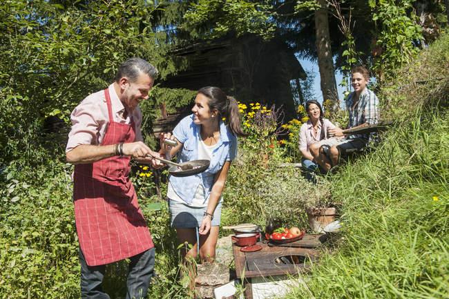 Eltern kochen für Kinder am ländlichen Herd im Garten — Stockfoto