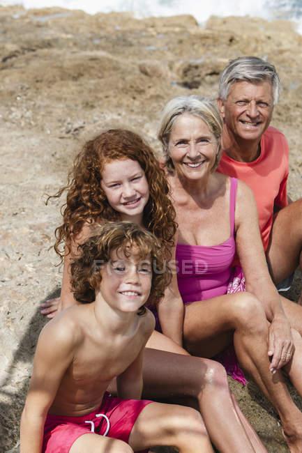 Grands-parents avec petits-enfants assis sur la plage — Photo de stock