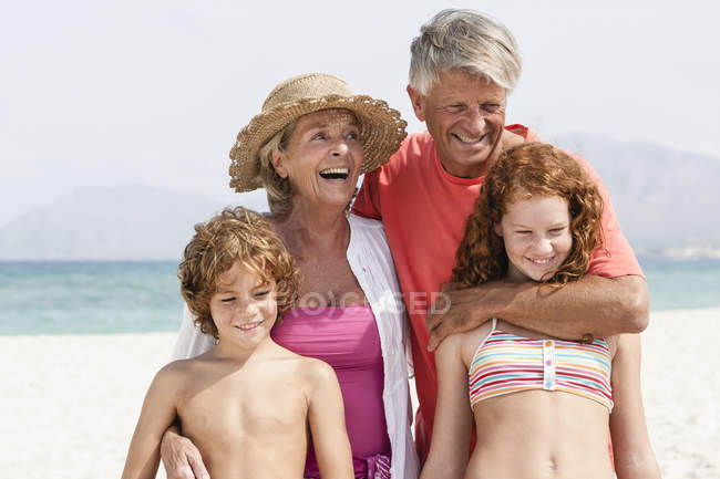 Großeltern mit Enkeln am Strand — Stockfoto