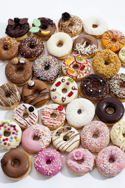 Many sweet colorful doughnuts on white background — Stock Photo