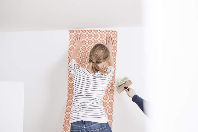 Donna attaccare carta da parati sul muro — Foto stock