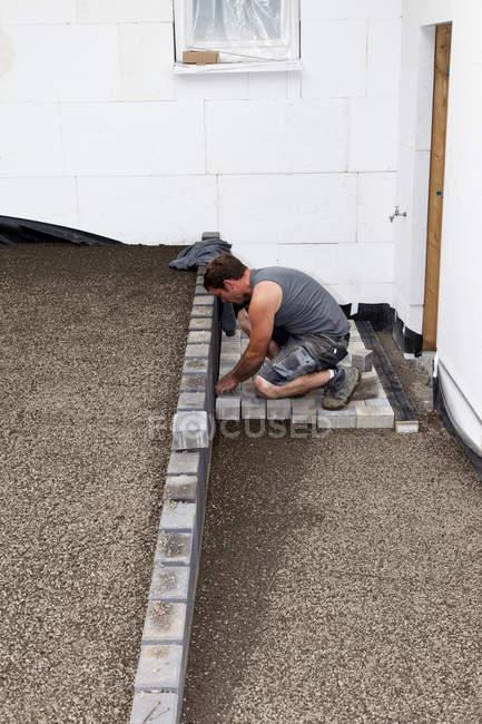 Man assembling paving stone on construction site — Stock Photo