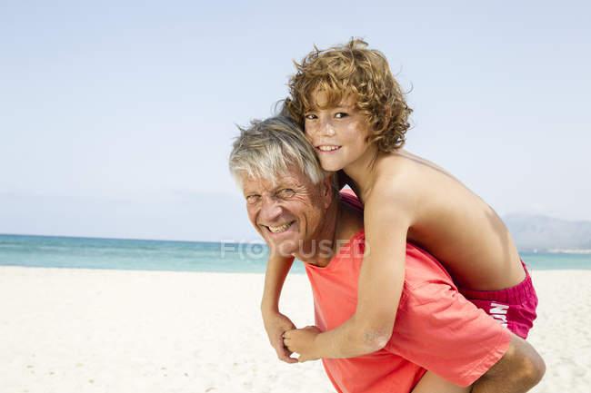Grandfather giving piggyback ride to grandson — Stock Photo