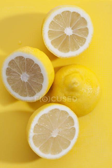 Limões frescos cortados pela metade na placa de plástico amarelo — Fotografia de Stock