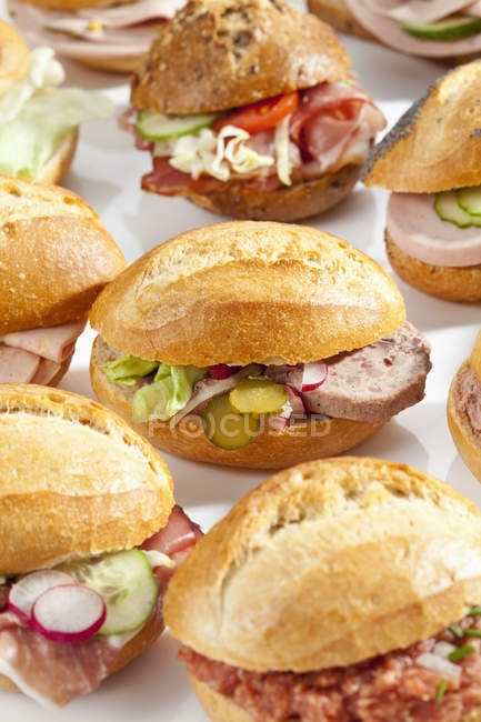 Variety of bread rolls sandwiches with mixed cold cuts on white background, close up — Stock Photo