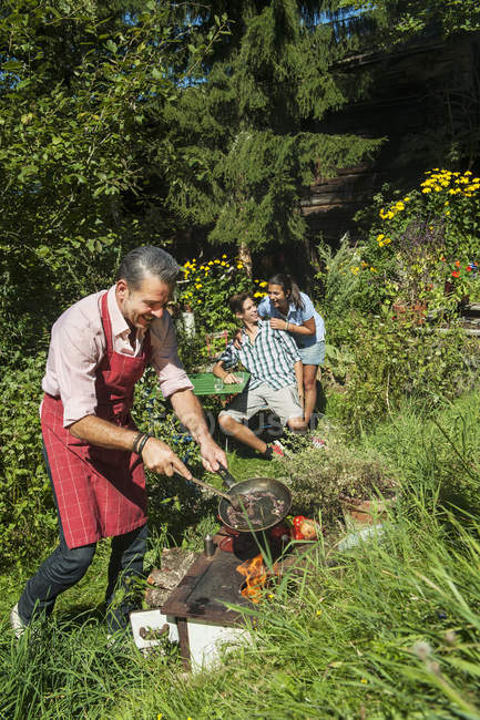 Homme cuisine pour les enfants sur le poêle rural dans le jardin — Photo de stock